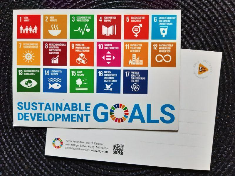 Das Bild zeigt zwei übereinanderliegende Postkarten. Auf der oberen Postkarte sind die 17 Ziele für nachhaltige Entwicklung abgebildet.