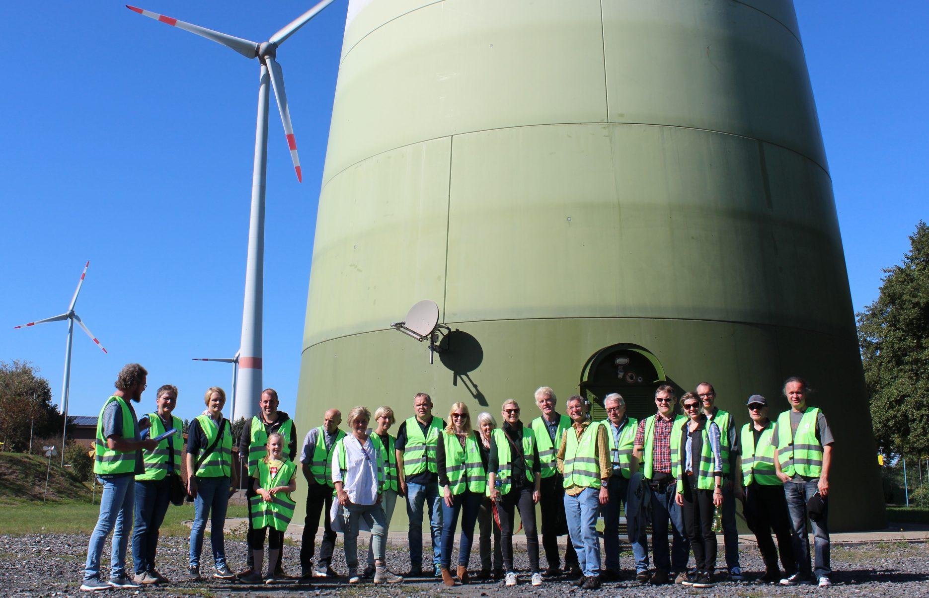 Das Bild zeigt eine Gruppe von Personen in Warnwesten, Teilnehmende des Projektes Klimaschutzbürger 2.0, die am Fuße eines Windrades stehen
