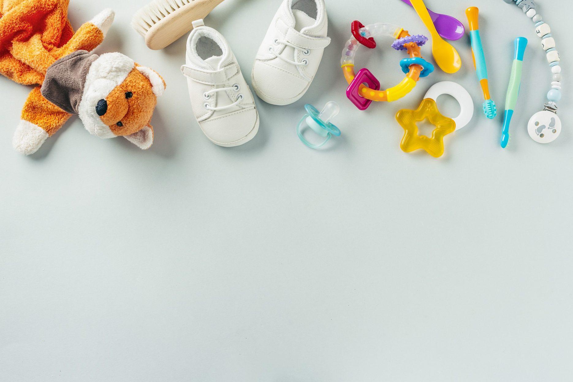 Das Bild zeigt verschiedene, bunte Baby-Sachen: Fuchs-Kuscheltier, Haarbürste, Schuhe, Spielzeug, Schnuller und Schnullerkette, Zahnbürsten, Löffel.