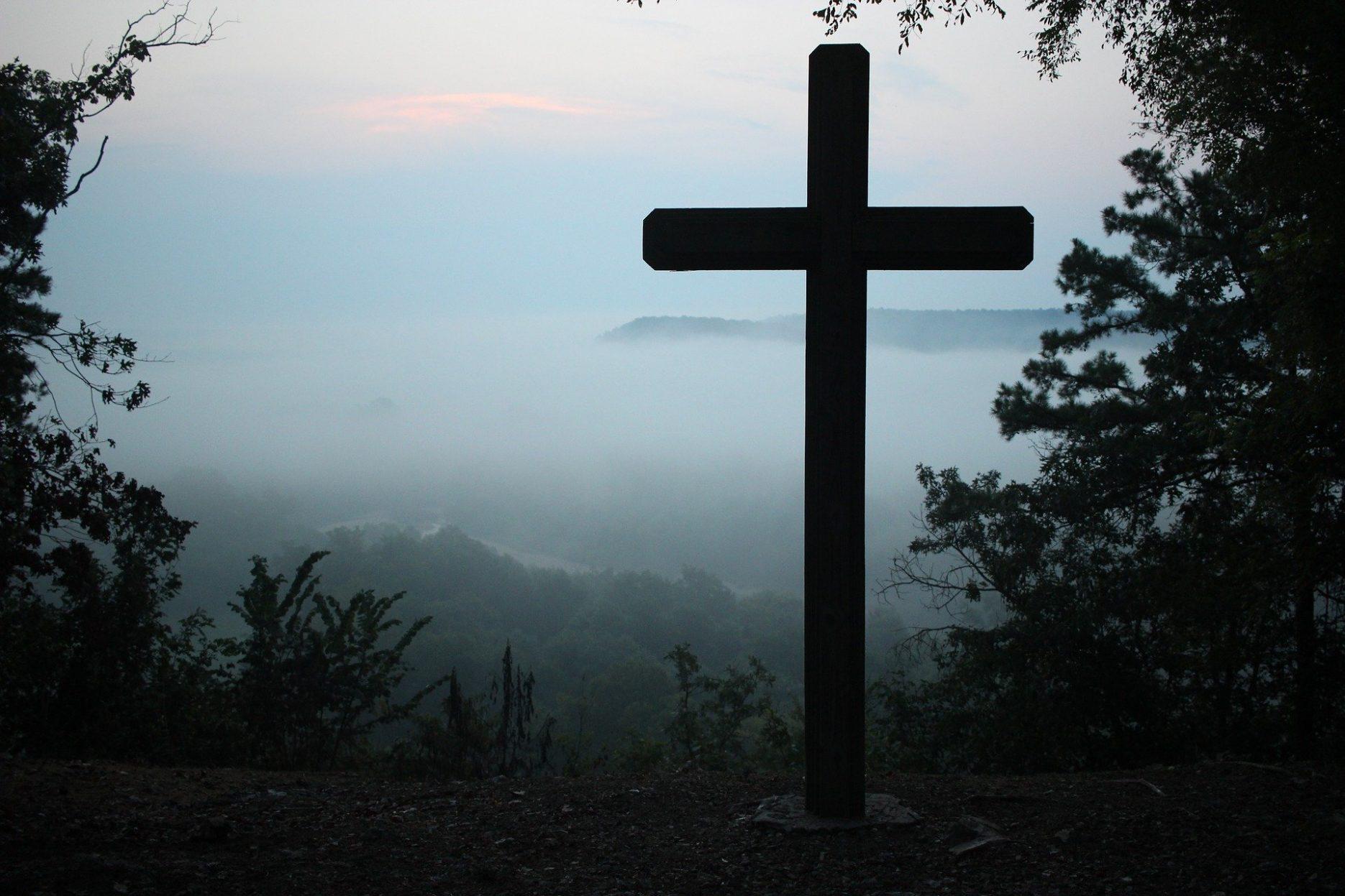 Das Bild zeigt ein großes Kreuz, das auf einem bewaldeten Berg aufgestellt ist. Im Hintergrund liegt das von Nebel bedeckte Tal.