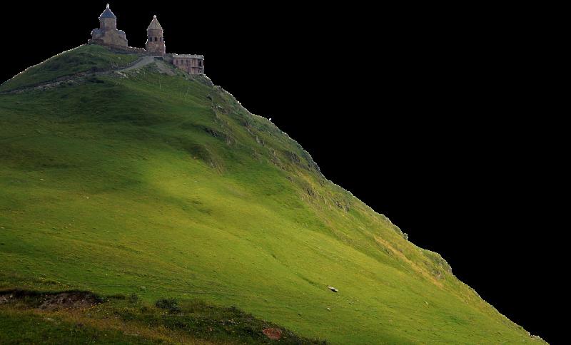 Das Bild zeigt ein Kloster auf der Spitze eines grün bewachsenen Berges.
