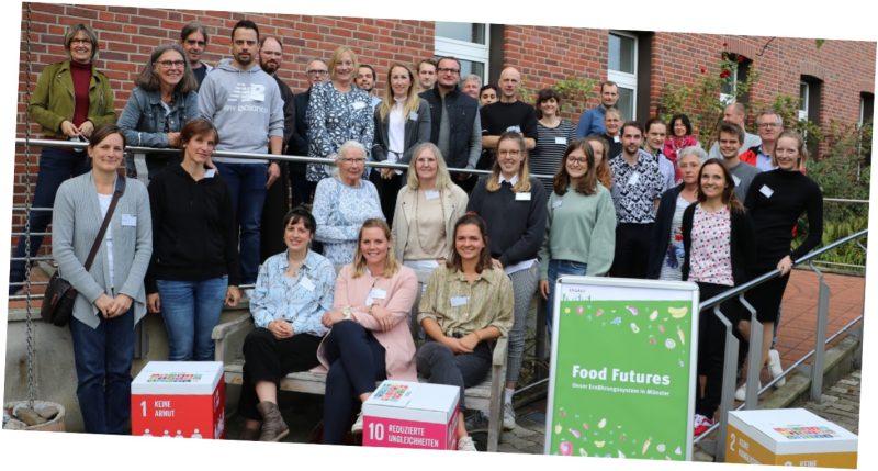 """Das Bild zeigt die Leitung, die Teilnehmenden und die Expert*innen des Bürgerdialogs """"Food Futures: Unser Ernährungssystem in Münster""""."""
