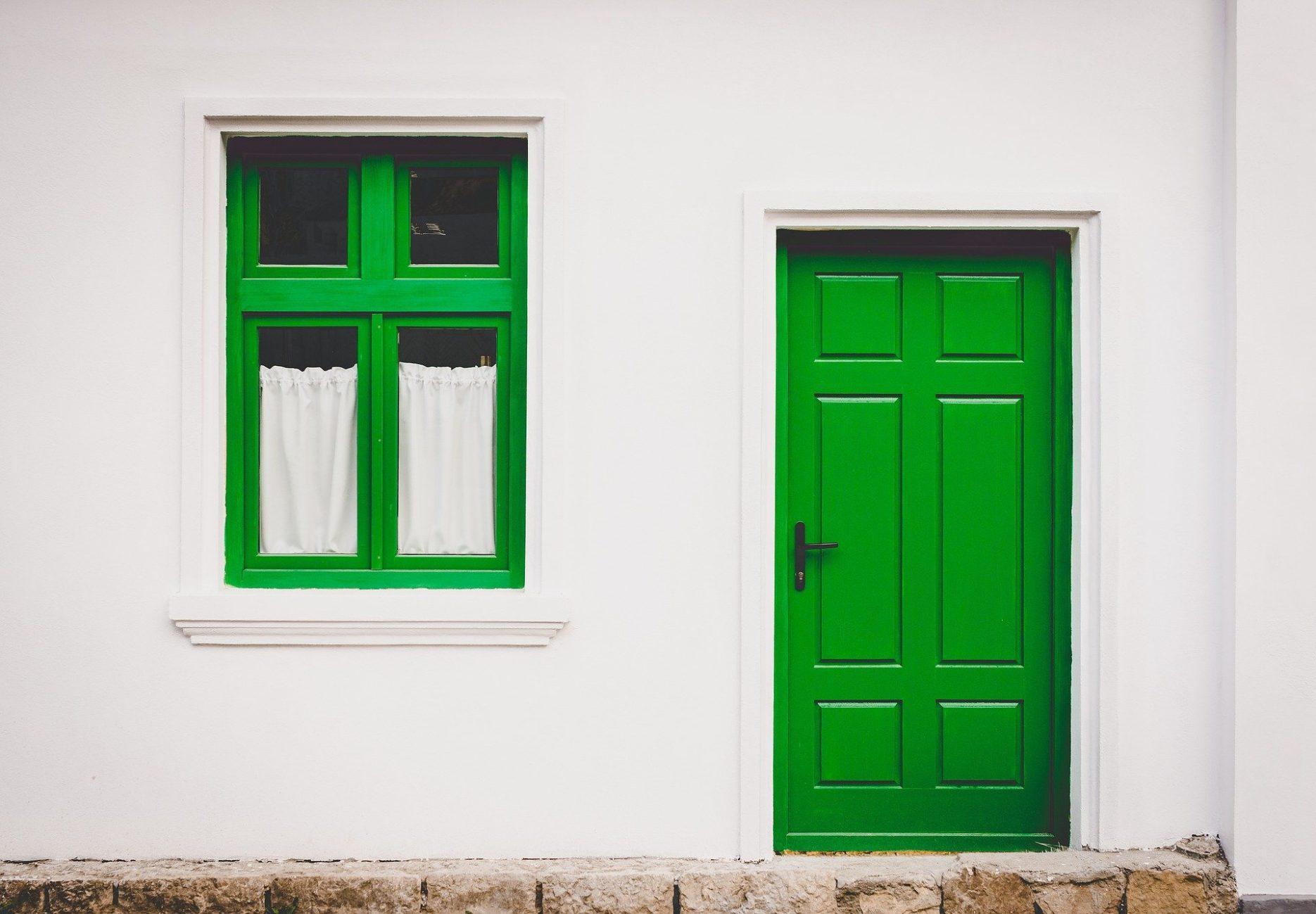 Das Bild zeigt ein Haus mit einfacher grüner Tür und grünem Fenster.